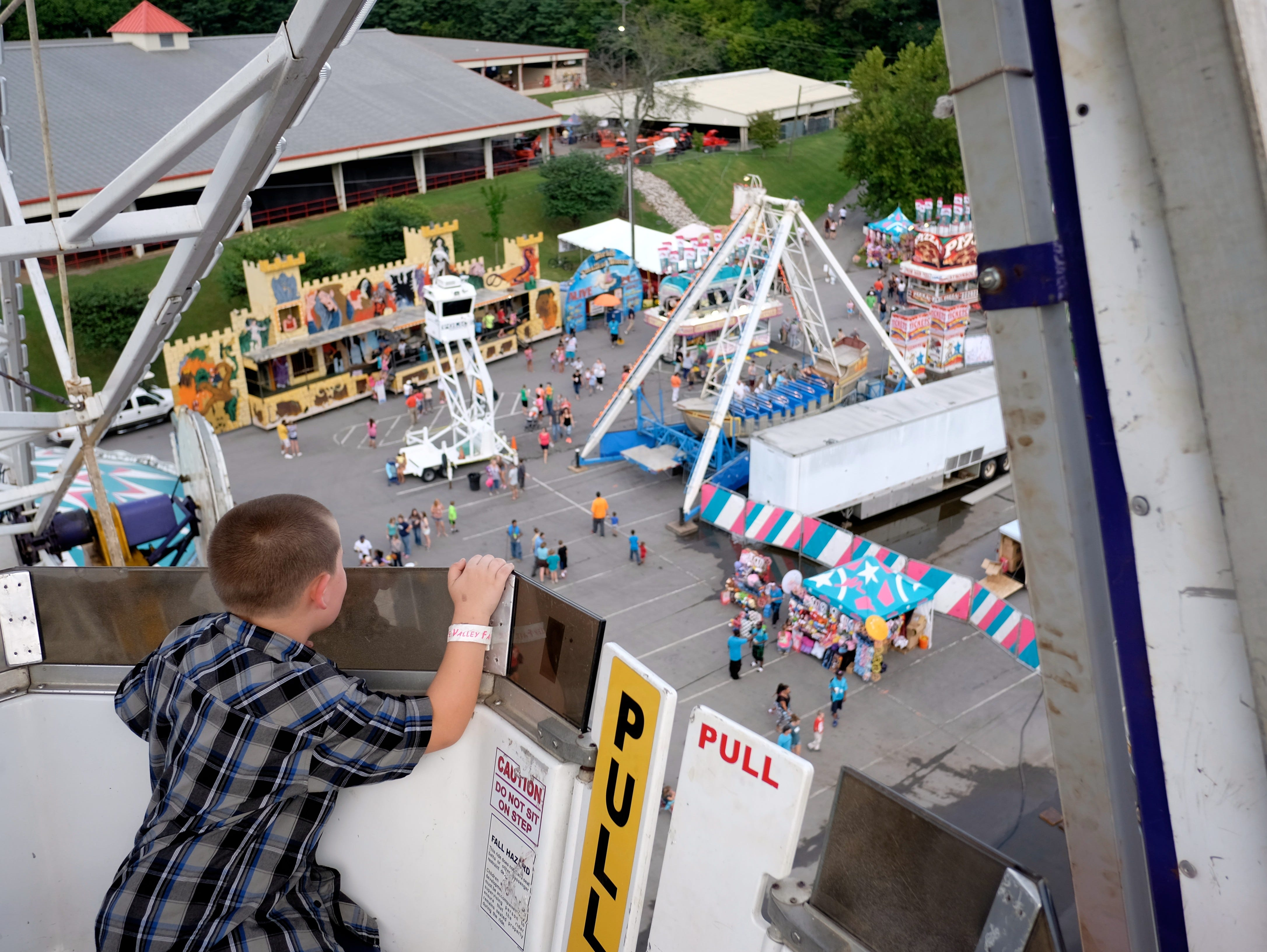 Fair goer Jacob Poor, 6, looks over the edge of a ferris wheel  during the 2014 Tennessee Valley Fair in Knoxville, Tenn., on Friday, September 5, 2014.