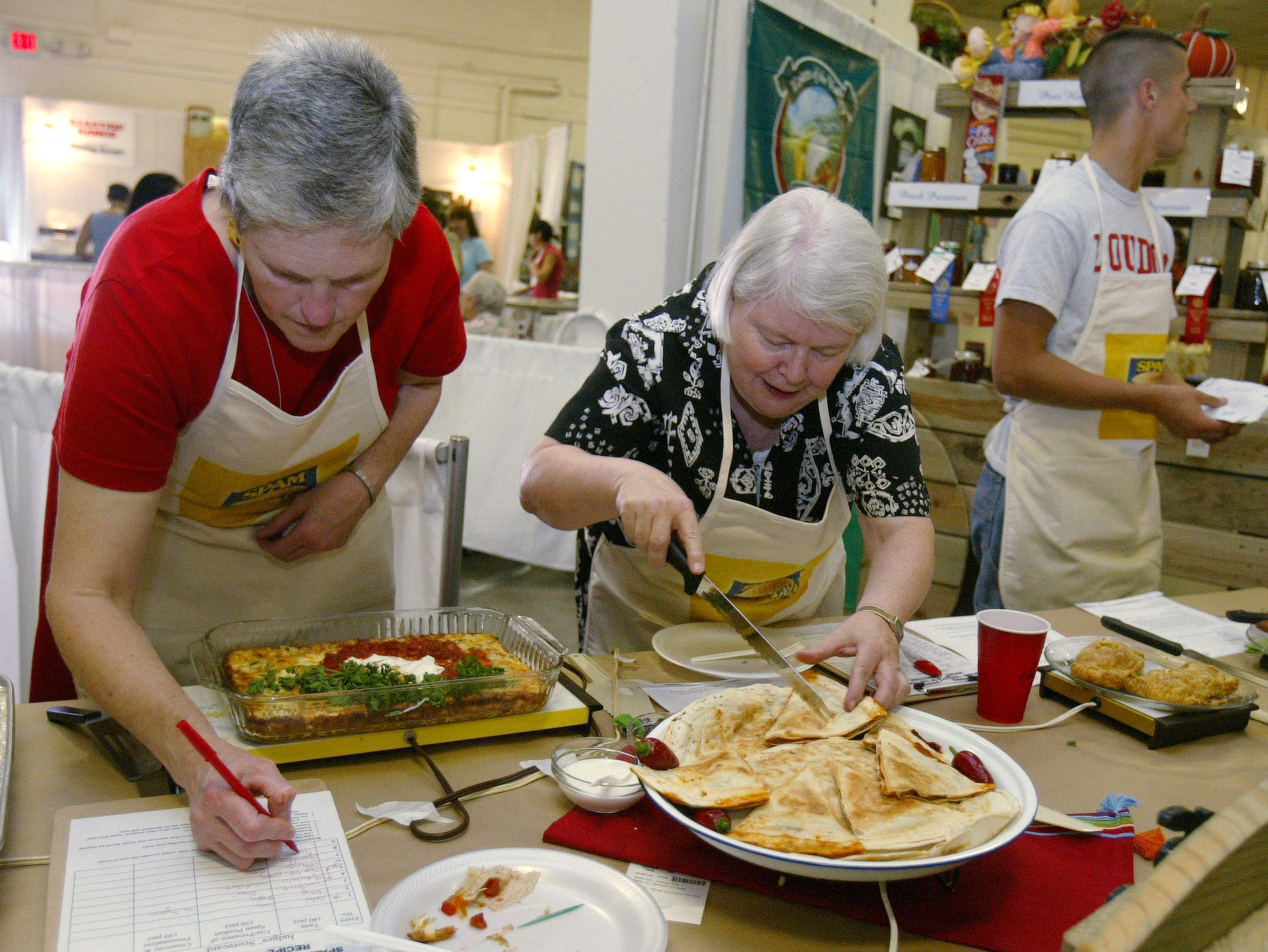 Lynda Rizzardi, left, takes notes while Etta Mae Westbrook samples Spamadillas made by David Shankles. The women were judging the Spam Kid Chef of the Year Cook-off held Sunday at the Tennessee Valley Fair in 2005.