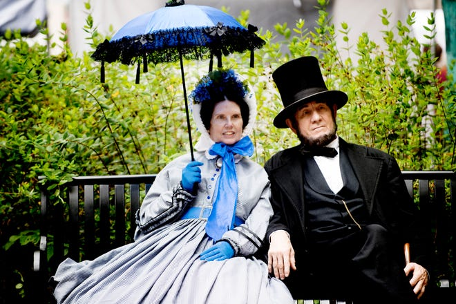 """Abraham and Mary Todd Lincoln rest on a bench at the East Tennessee Historical Society History Fair in downtown Knoxville, Tennessee on Saturday, August 18, 2018. The fair included a variety of antiques, crafts, historical actors and a """"history hound"""" dog costume contest."""