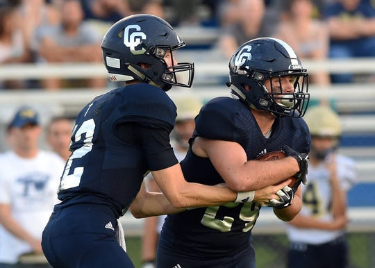 Central Catholic quarterback Wes Dulin hands off to fullback Adam Dienhart.