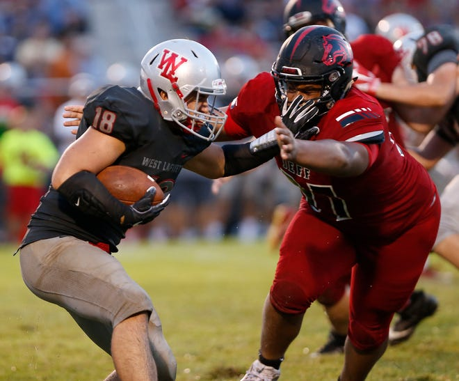 Sage Hood of West Lafayette is wrapped up by Peyton Price of Lafayette Jeff Friday, August 17, 2018, at Gordon Straley Field in West Lafayette. West Lafayette defeated Jeff 38-29.