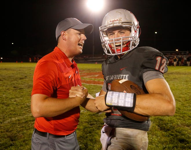 West Lafayette head coach Shane Fry celebrates with quarterback Kyle Adams after the Red Devils defeated Lafayette Jeff 38-29 Friday at Gordon Straley Field in West Lafayette.