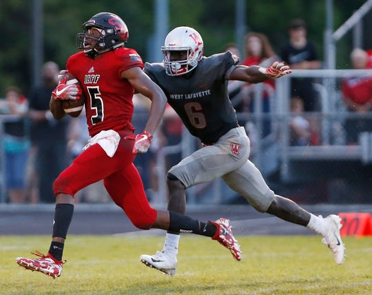 Brian Jenkins of Lafayette Jeff nearly escapes the grasp of Nelson Mbongo of West Lafayette Friday night.