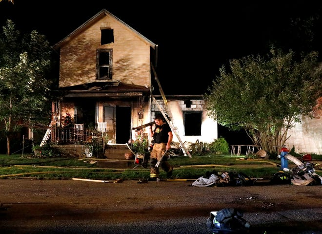 A Lancaster firefighter gathers equipment Friday night, Aug. 17, 2018, from in front of a house in the 600 block of East Mulberry Street in Lancaster. According to fire officials a man who lives at the house was taken to Fairfield Medical Center to be treated for smoke inhalation.