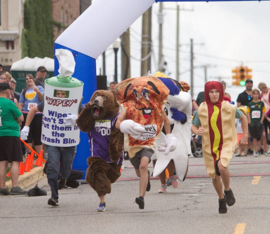 Mascots from a variety of groups, schools and businesses take to the first of two laps of the Mascot Dash Friday, Aug. 17, 2018.