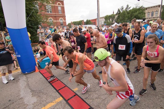 Leading off the start of the Melon Run are 5K winner Patrick Miller in the orange tank top and 10K winner Clayton Woll in the green hat on Friday, Aug. 17, 2018.