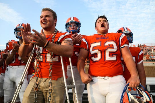 Devon Evans, left, and Dalton Keeling cheer on  their team as the Marshall County High Marshals played against Ft. Campbell Friday, Aug. 17 in Benton, Ky. Both are juniors and were shot during the January 23 school shooting that killed two of their classmates.
