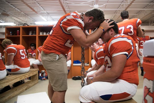 Devon Evans gives his friend and teammate Dalton Keeling words of encouragement before the Marshall County High School football season opener Friday, Aug. 17 in Benton, Ky. Both are juniors and were shot during the January 23 school shooting which killed classmates Bailey Holt and Preston Cope, both who were 15.