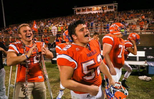 Devon Evans, left, and Dalton Keeling celebrateo as their Marshall County High Marshals defeat Ft. Campbell 34-12 in the Marshals season opener Friday, Aug. 17 in Benton, Ky. Both are juniors and were shot during the January 23 school shooting which killed Bailey Holt and Preston Cope.