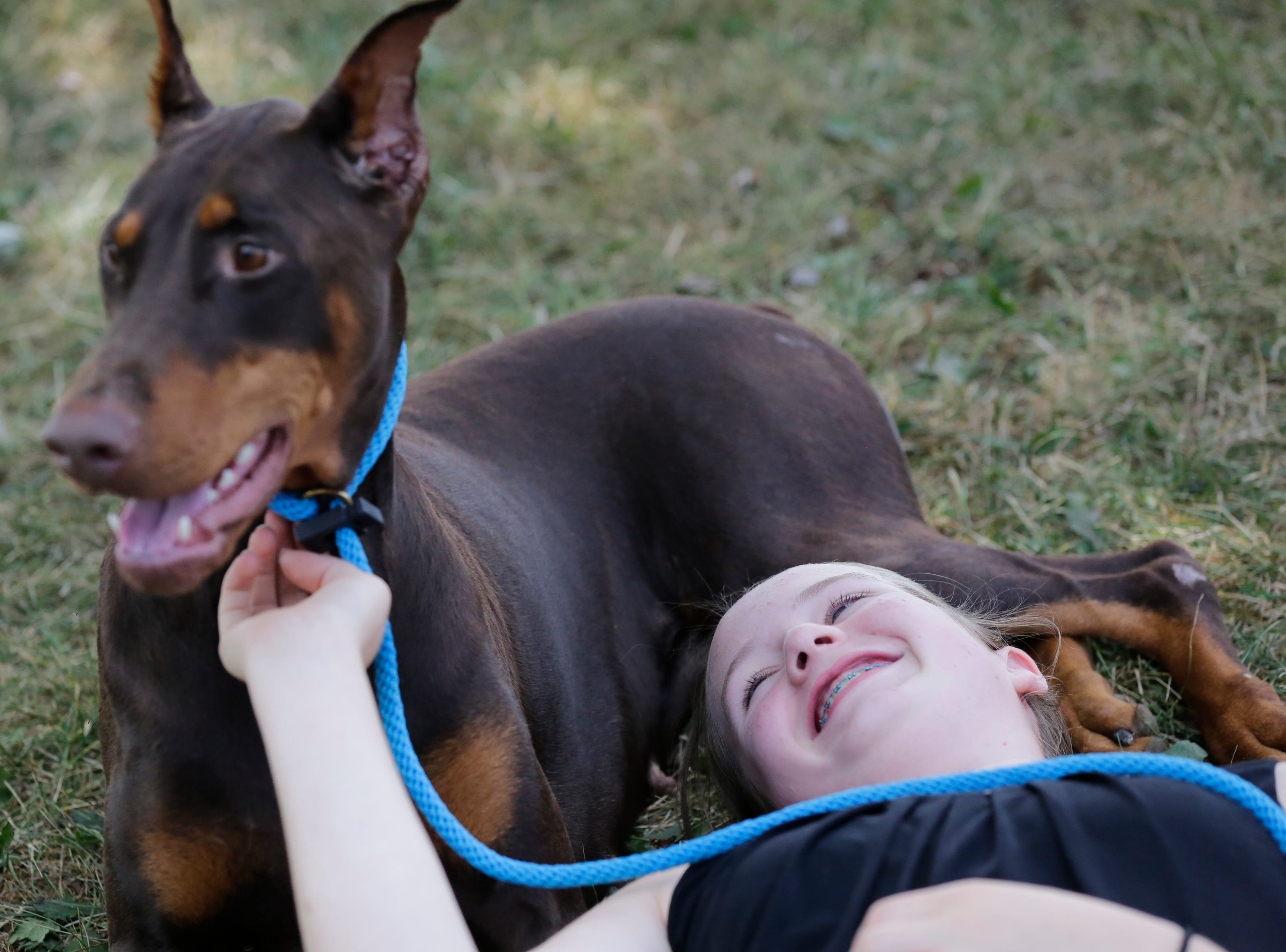 Katelyn Heiman cuddles in the grass with her Doberman pinscher Abby before competing during the Marshfield Area Kennel Club's All-Breed Dog Show, Obedience Trials and Rally Trials at the Central Wisconsin Fairgrounds in Marshfield Saturday, August 18, 2018.