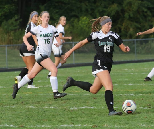 Clear Fork's MacKenzie Thorne kicks the ball down the field in front of Madison's Caitlyn Zeigler on Friday night.