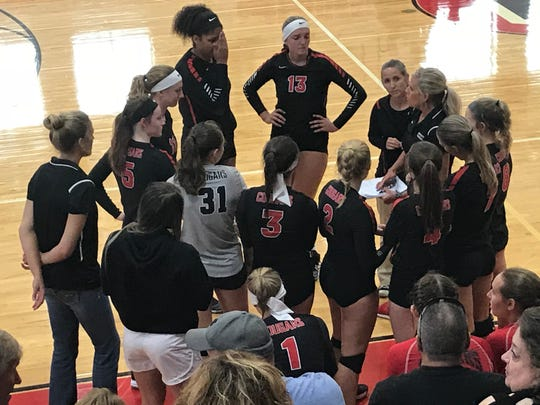 The Crestview Lady Cougars talk with head coach Jody Ritchey before the third set of their match with the Buckeye Central Buckettes.