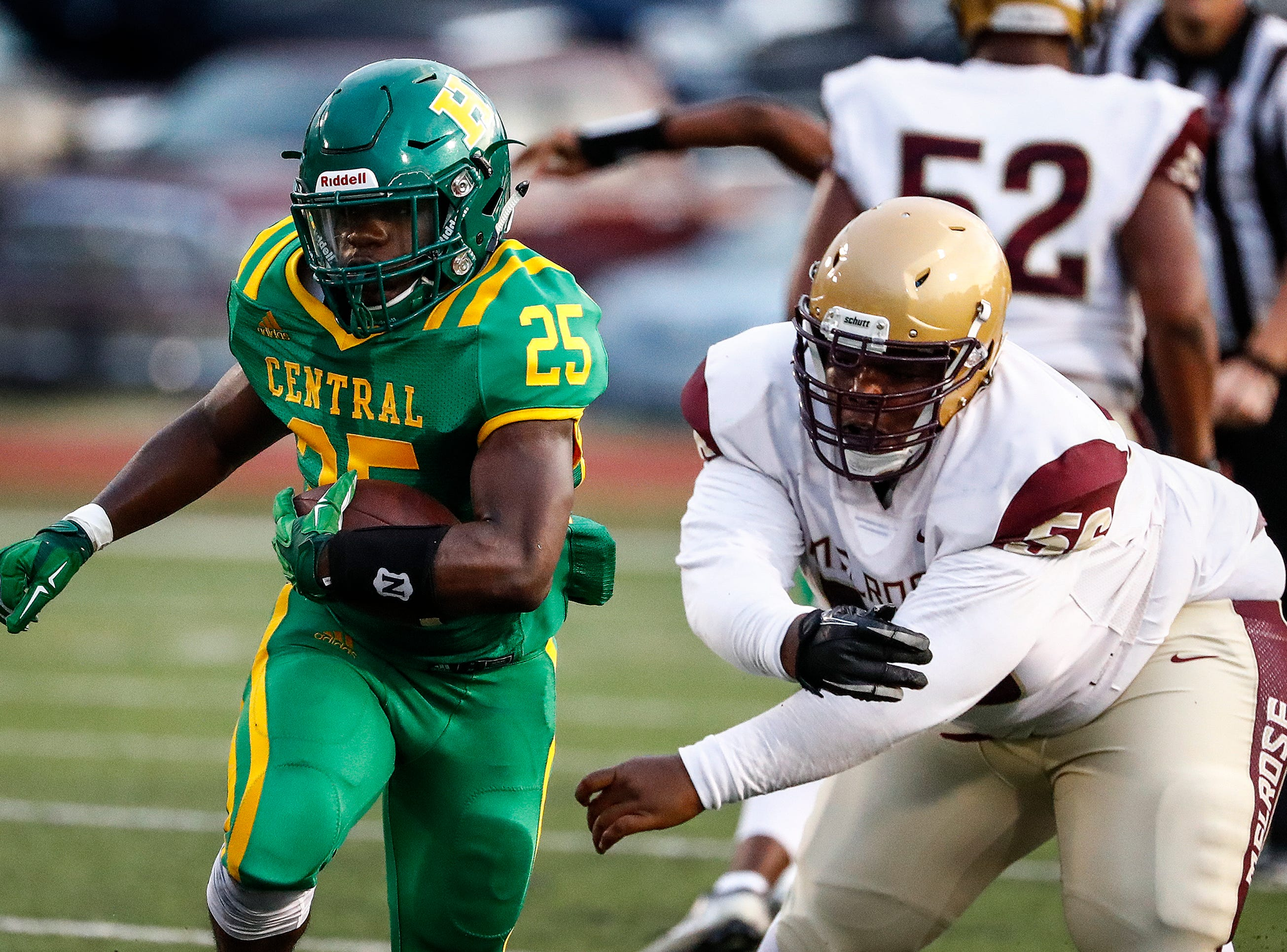 Central running back Alan Thornton (left) runs away from Melrose defender LeKelvin Boodie (right) during action of the season opener on Friday, Aug. 17, 2018, at Crump Stadium.