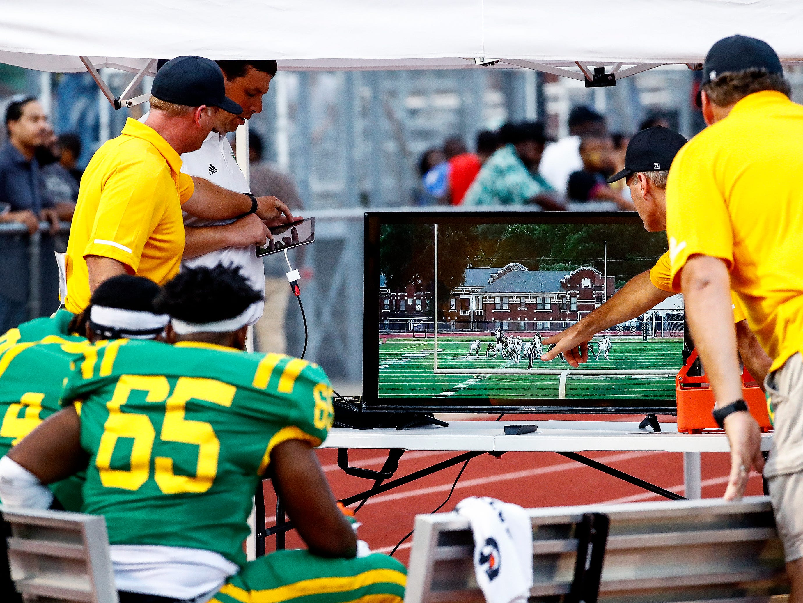 Central coaches go over footage of defenses action on the sidelines during the season opener against Melrose on Friday, Aug. 17, 2018, at Crump Stadium.