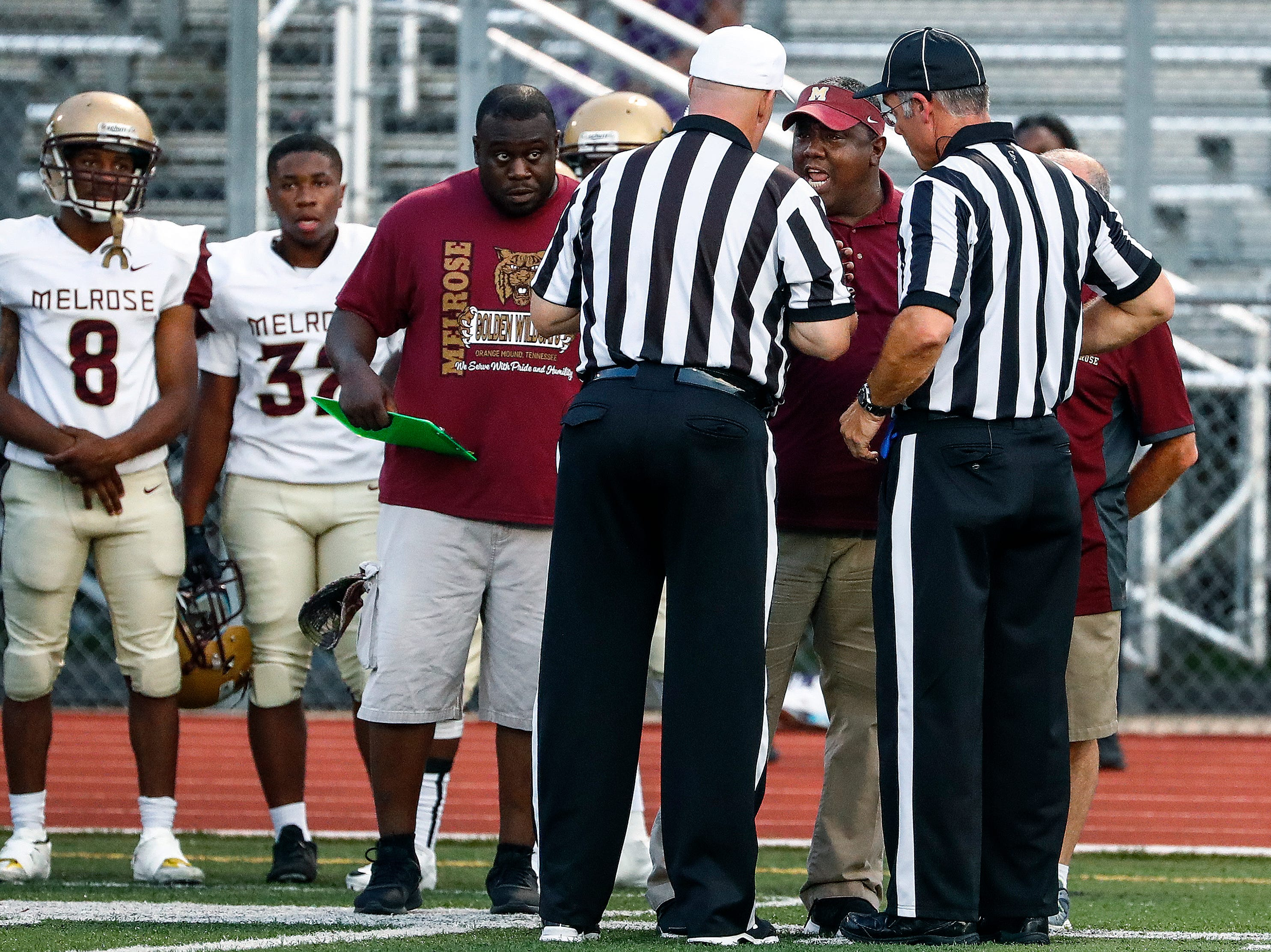 Melrose head coach Ronald Davis (middle) talks with the officials during the season opener against Central on Friday, Aug. 17, 2018, at Crump Stadium.