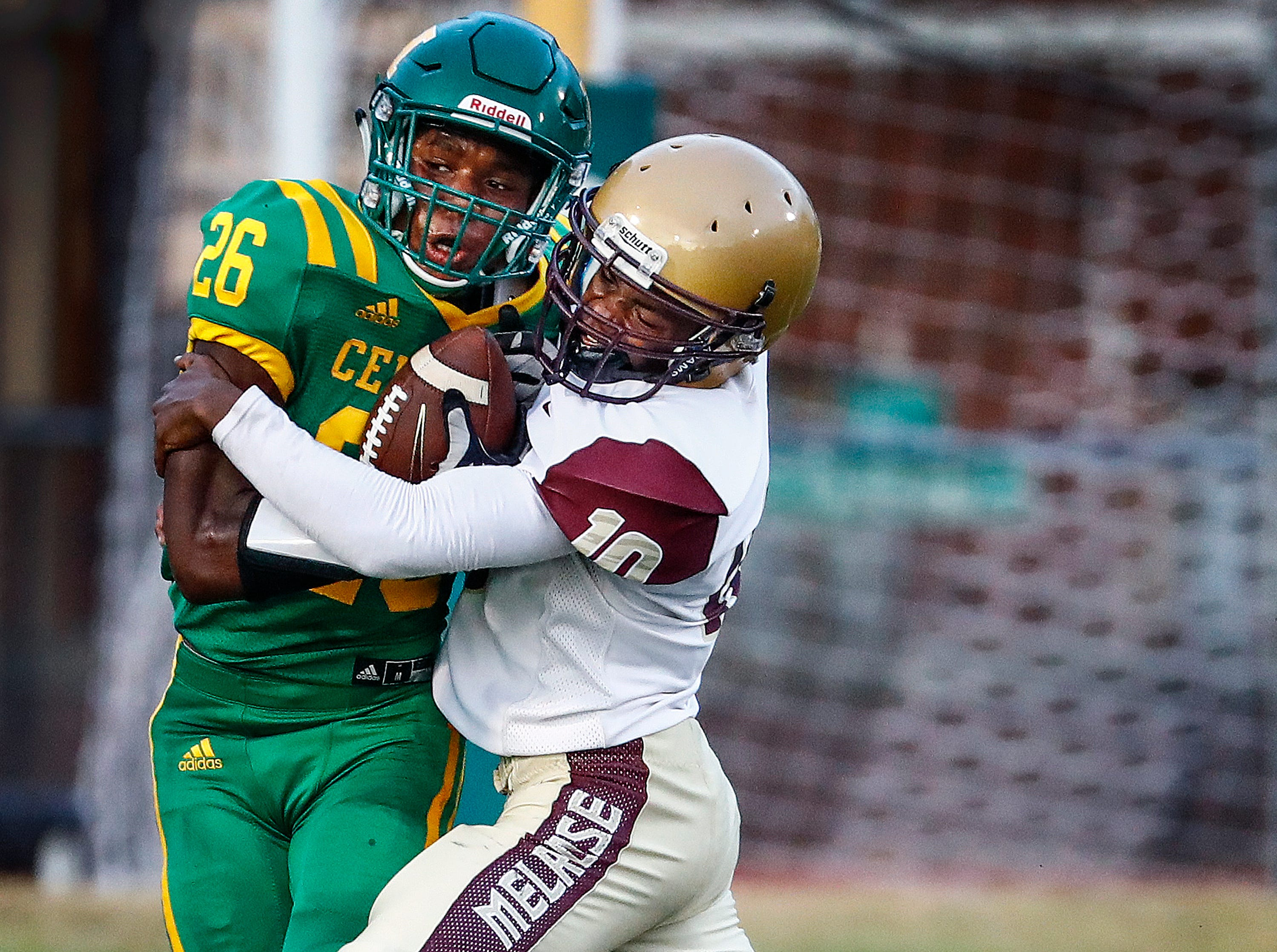 Central receiver Lorenzo Towns (left) is brought down by Melrose defender Donterrius Taylor (right) during action of the season opener on Friday, Aug. 17, 2018, at Crump Stadium.