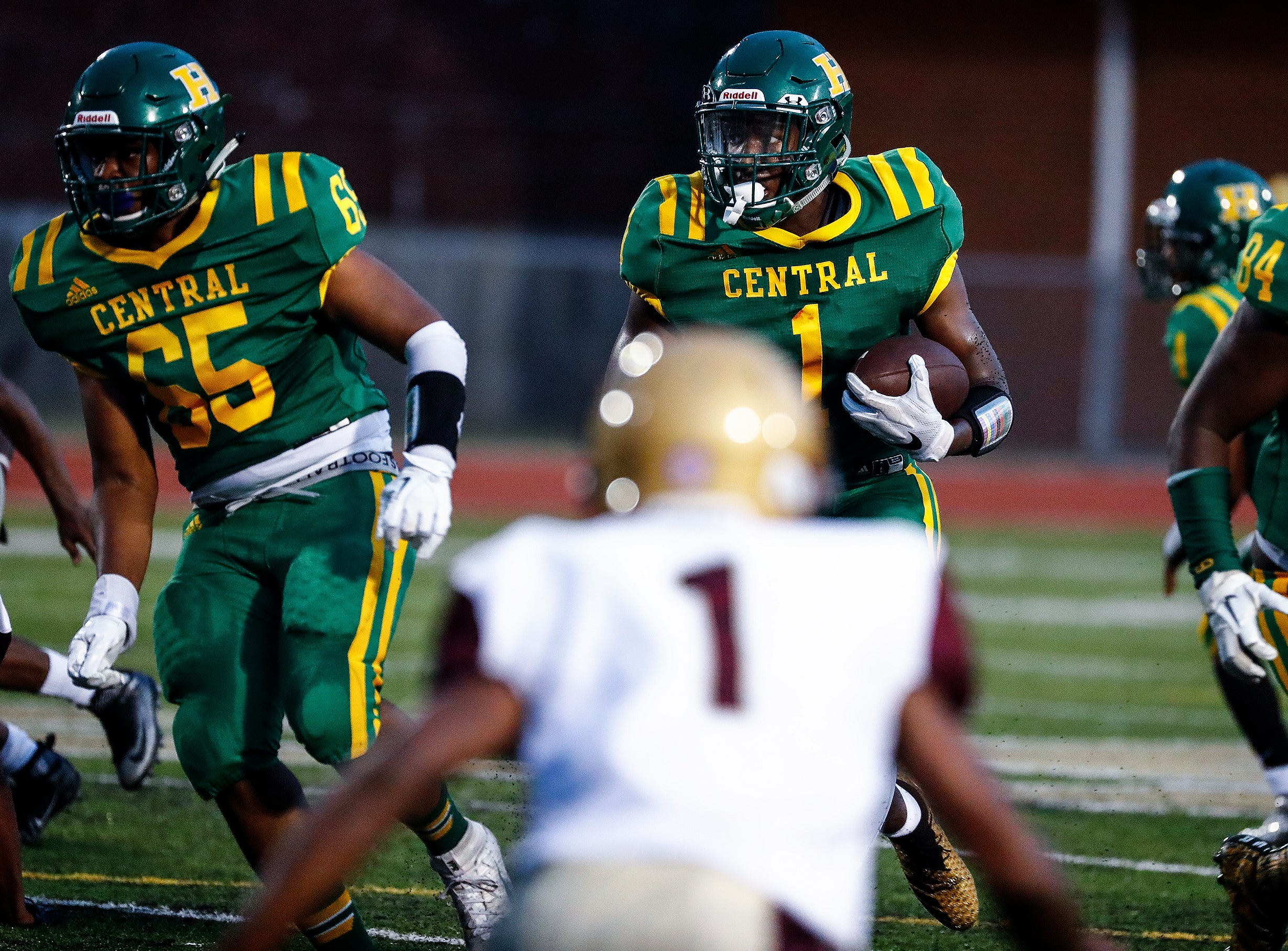 Central running back Dylan Ingram (middle) finds positive yards against the Melrose defense during action of the season opener on Friday, Aug. 17, 2018, at Crump Stadium.