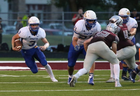 Germantown quarterback Connor Leffler heads up the field on a keeper against the Menomonee Falls defense Friday night.