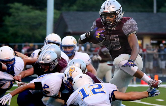 Menomonee Falls' Julius Davis attempts to hurdle the Germantown defensive line at Menomonee Falls on Aug. 17.