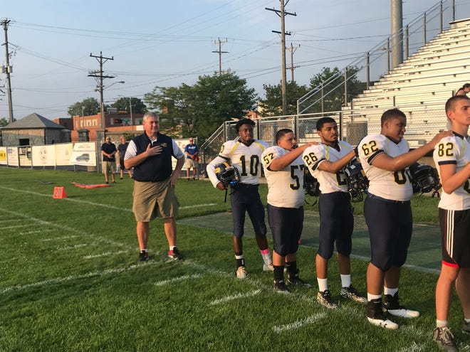 Former Pius XI standout John Rasmussen stands for the national anthem before his first game as head coach at Horlick Field against Racine Park Friday Aug. 17, 2018.