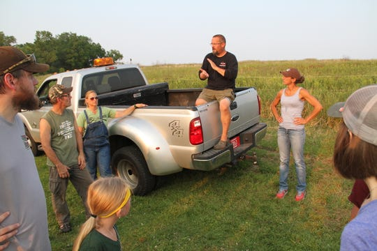 Paul Samerdyke, a Department of Natural Resources wildlife biologist sits on the tailgate of a pick-up and thanks volunteers for participating in a duck banding outing at Horicon Marsh State Wildlife Area in Horicon.
