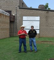 Baxter County Judge Mickey Pendergrass (left) and Sheriff John Montgomery speak at the groundbreaking Friday for the county's 50-bed expansion of the county jail.