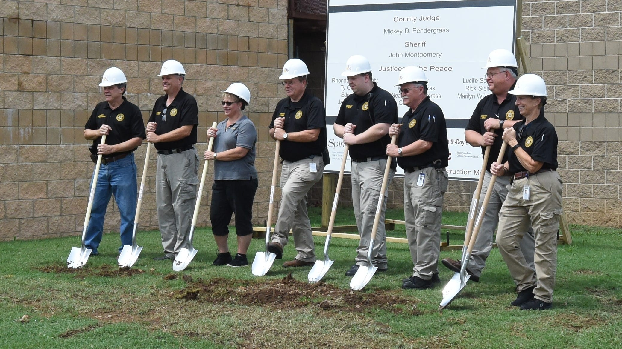 Members of the Baxter County Sheriff's Office take a turn Friday breaking ground on the site of the Baxter County Detention Facility's 50-bed expansion.