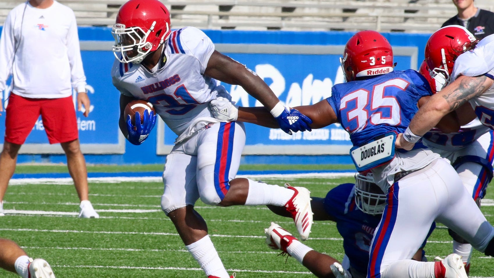 Louisiana Tech redshirt sophomore running back Justin Henderson (31) runs through a tackle during the team's second fall scrimmage Saturday at Joe Aillet Stadium.