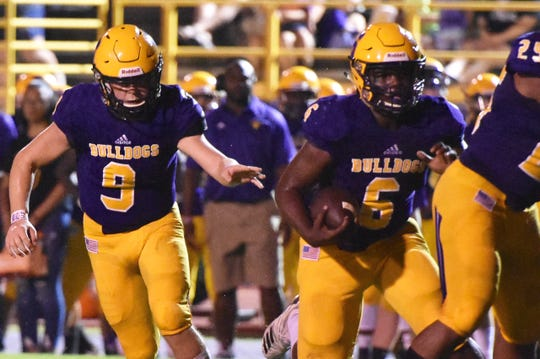 Smyrna's Mikel Hartfield (6) runs the ball while quarterback Alex Bannister (9) follows during Friday's 41-0 win over La Vergne.