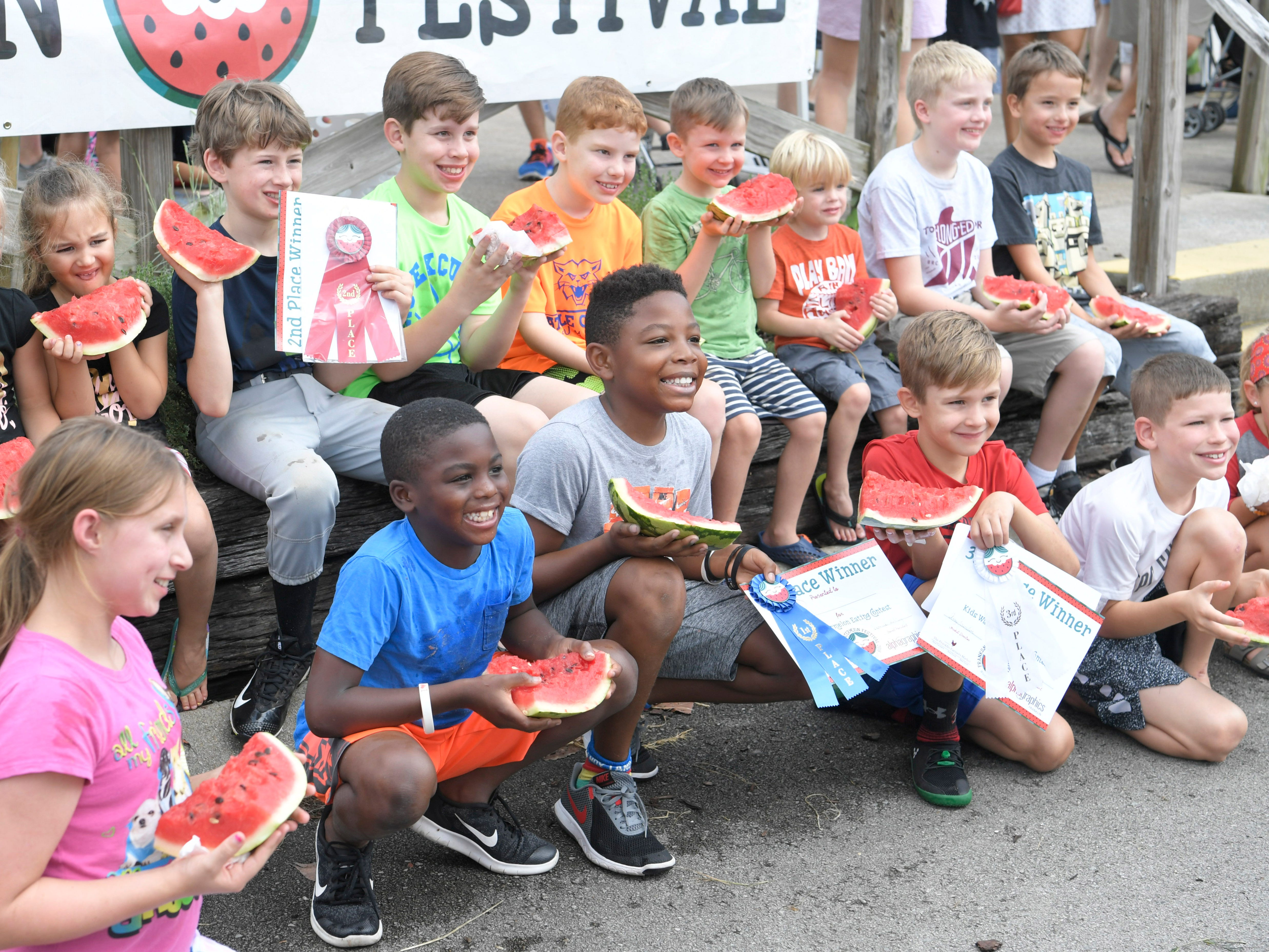 Children pose for a photograph after competing in the Franklin Watermelon Festival's watermelon eating contest at the Franklin Farmers Market in Franklin, Tenn. on Saturday, August 18, 2018.