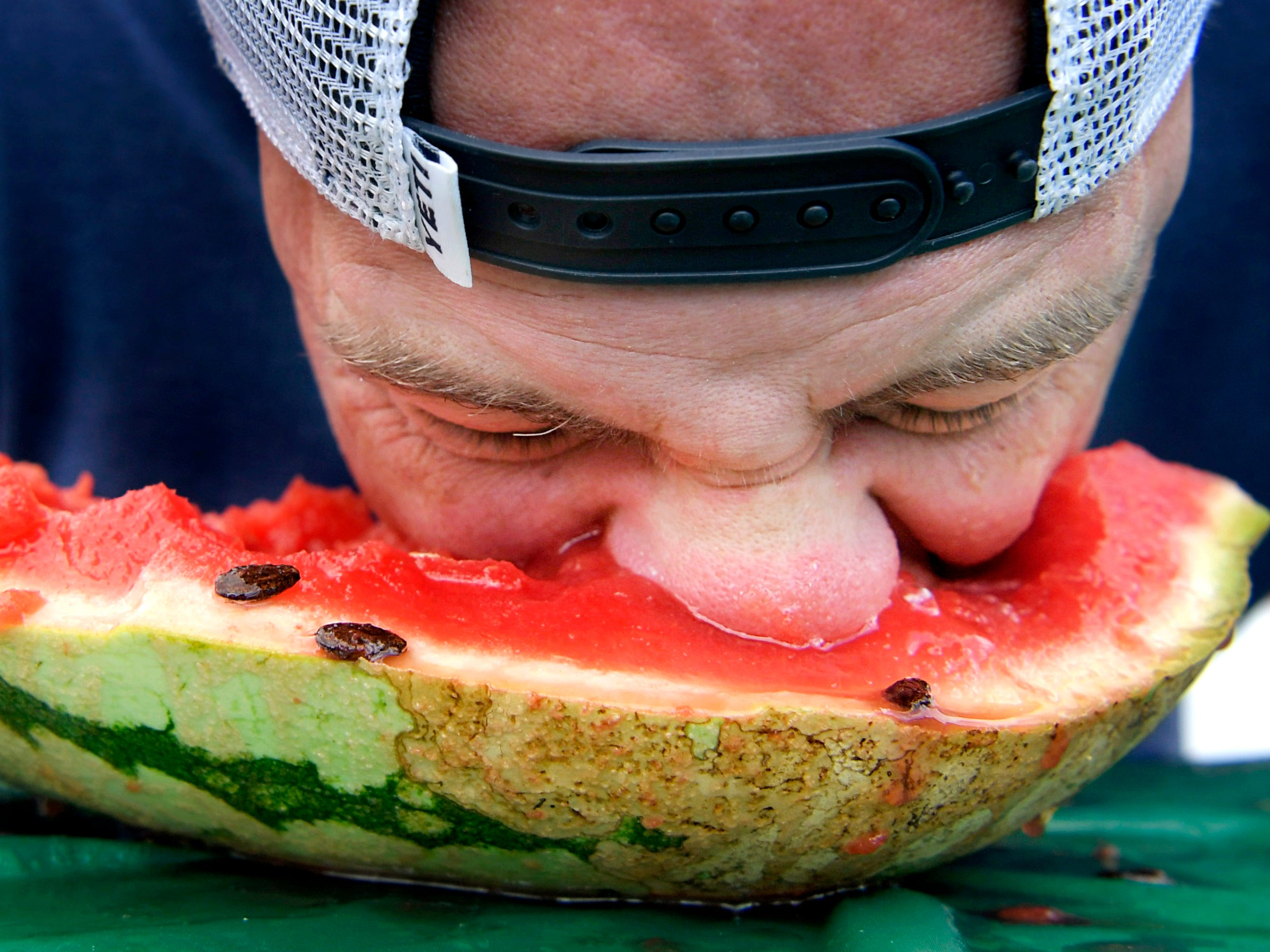 Tim Malone competes in the adult watermelon eating contest during the Franklin Watermelon Festival at the Franklin Farmers Market on Saturday, Aug. 18, 2018.