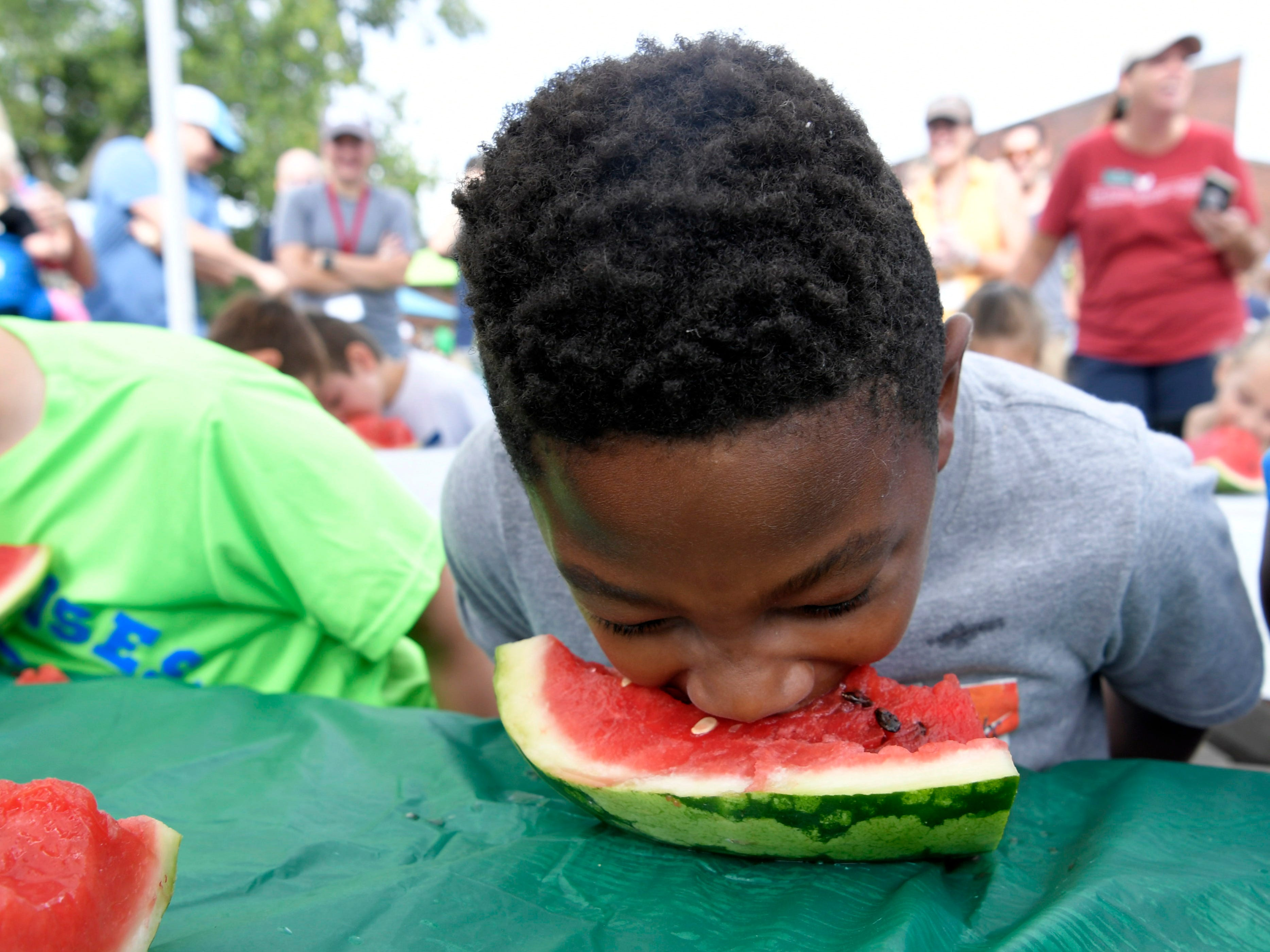 Shamaroin Cooksey,10, competes in the children's watermelon eating contest at the Franklin Farmers Market in Franklin, Tenn. on Saturday,  August 18, 2018.