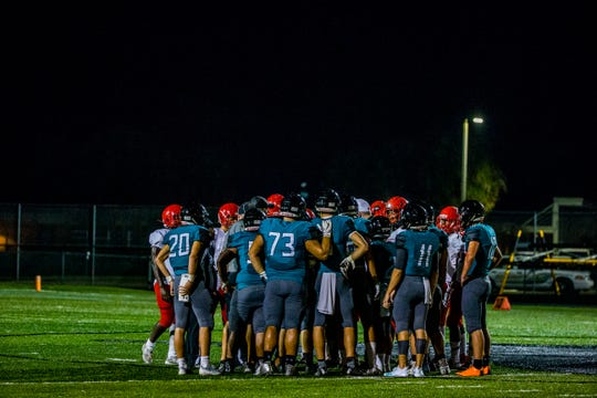 Gulf Coast and Immokalee players huddle together during the preseason game at Gulf Coast High School on Friday, Aug. 17, 2018.