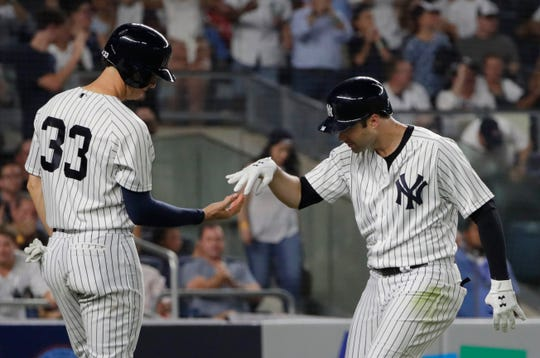 New York Yankees' Neil Walker, right, celebrates with teammate Greg Bird after they scored on Walker's three-run home run during the fourth inning of a baseball game against the Toronto Blue Jays, Friday, Aug. 17, 2018, in New York.