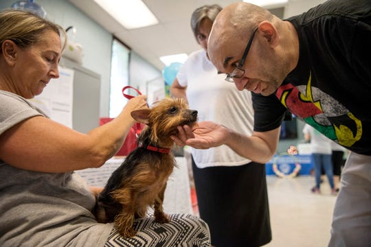 "A pet adoption drive at Bergen County Animal Shelter on Saturday, August 18, 2018. (right) Erick Kaslov pets ""Hershey."""