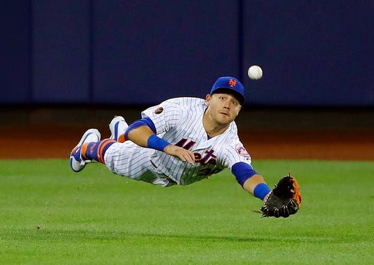 FILE - In this  June 23, 2018 file photo New York Mets center fielder Michael Conforto dives for but can't make the play on a ball hit by Los Angeles Dodgers' Yasiel Puig during the eighth inning of a baseball game in New York. Some talented, young baseball players have competed at the Little League World Series over the last 71 years. Fifty-four have gone on to realize another dream _ making the majors. Conforto will be one of the three Little League veterans on hand when the Mets play the Phillies in central Pennsylvania on Sunday, Aug. 19, 2018.