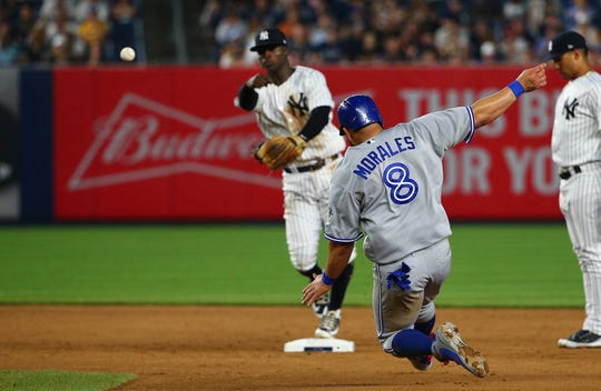 Yankees's shortstop Didi Gregorius turns a double play against the Blue Jays.