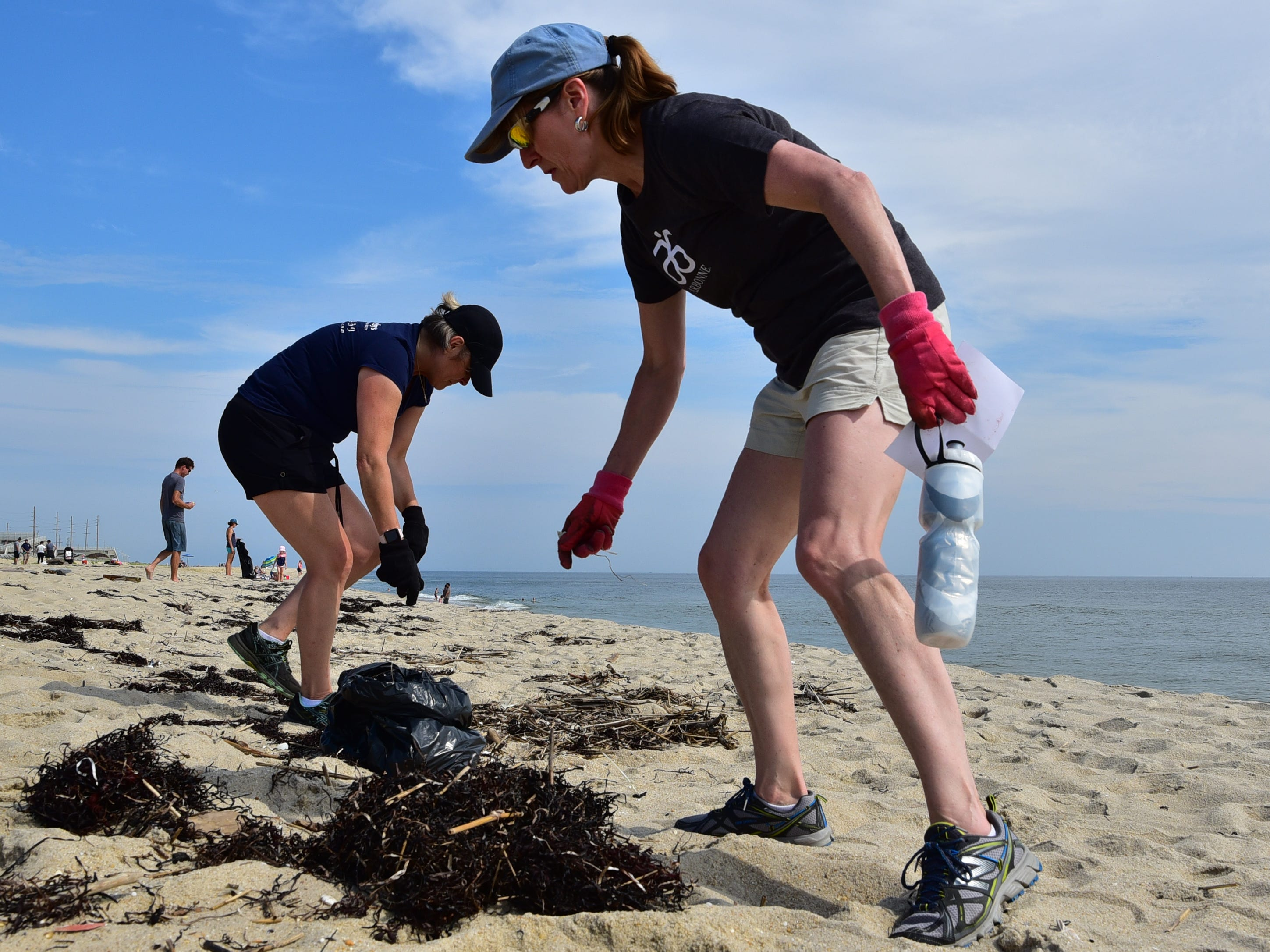 Volunteers Carol Wiatrak and Patty Kayane (front) pick up trash and plastic from the beach in Sea Bright on Saturday.