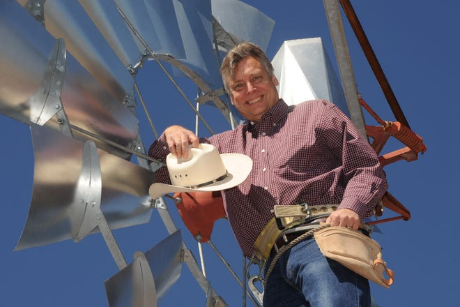 Robert Peterson poses atop a windmill at the NMSU Windpower Technoloy Center