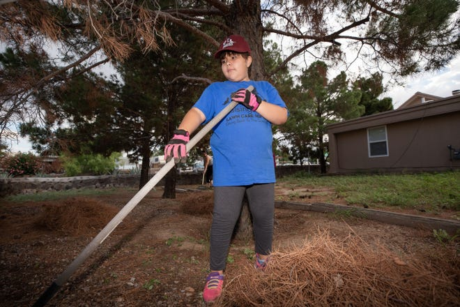 Natoria Martinez, 9, does yard work on a home on the 1500 block of Willow Street, Saturday, Aug. 18.