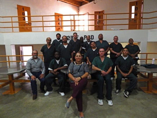 New Mexico State University Cooperative Extension Service agent Jeff Anderson, far left, and prison classification officer Sandra Lopez, center, pose with inmates in GOAL pod, who created a therapeutic garden program at the Southern New Mexico Correctional Facility in 2016.