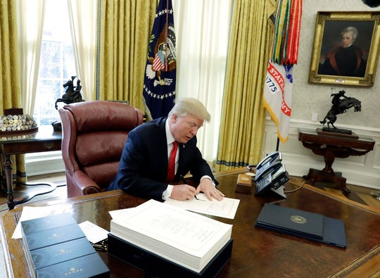 In this Dec. 22, 2017, file photo President Donald Trump signs into law a $1.5 trillion tax overhaul package in the Oval Office of the White House in Washington.