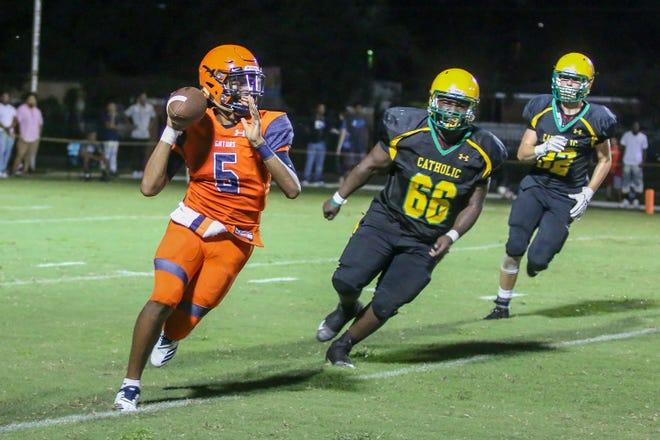 Escambia quarterback Aviaun Smith (5) runs outside of the pocket to throw the ball against Pensacola Catholic during a preseason three-school shootout at Catholic High School on Friday, August 17, 2018.