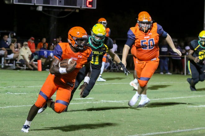 Escambia's Frank Peasent (1) races past the Pensacola Catholic defense during a preseason three-school shootout at Catholic High School on Friday, August 17, 2018.