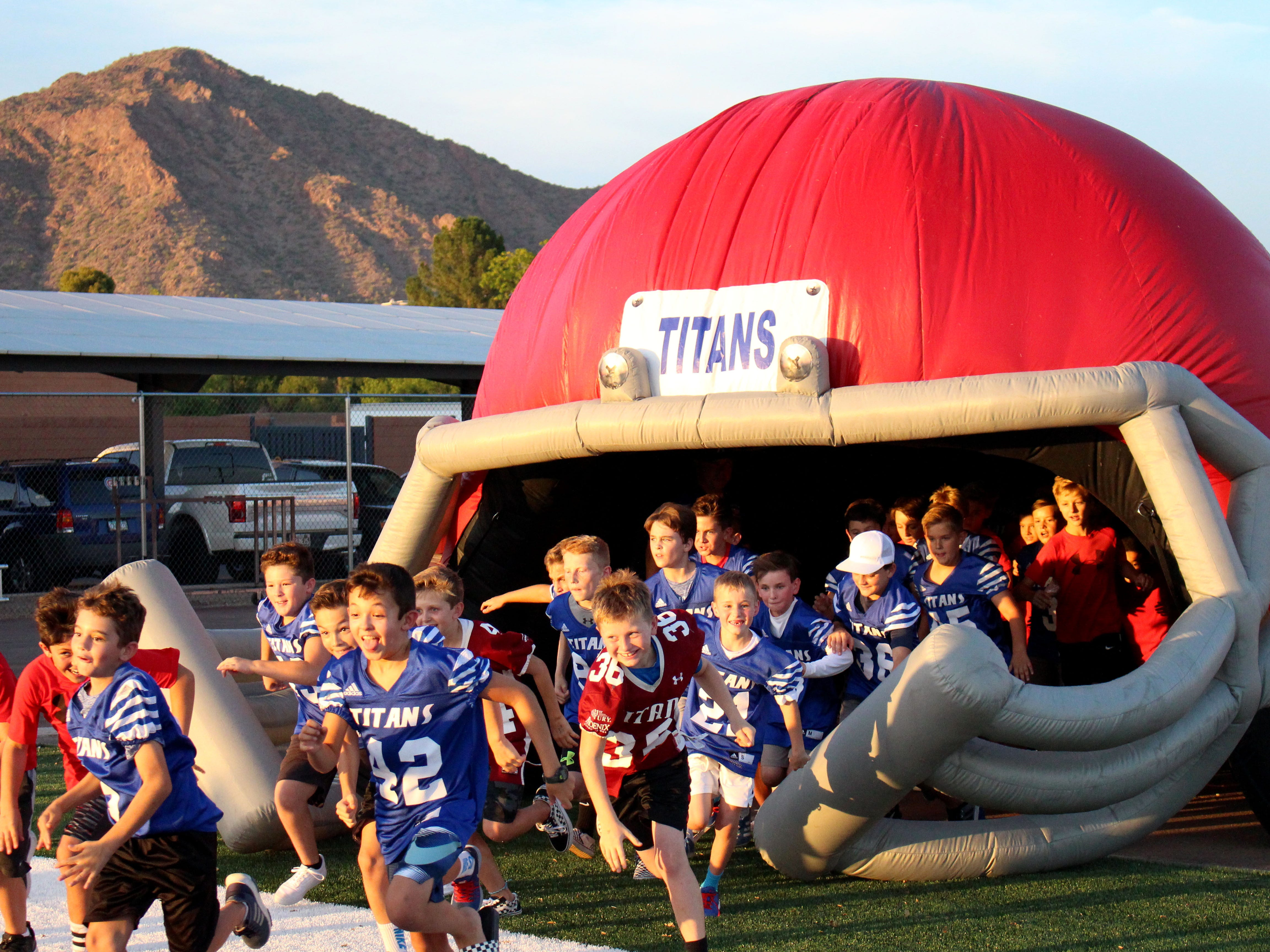 Kids run out onto the field before the Arcadia gets ready for its game against Coronado, Phoenix, Ariz. August 17, 2018.