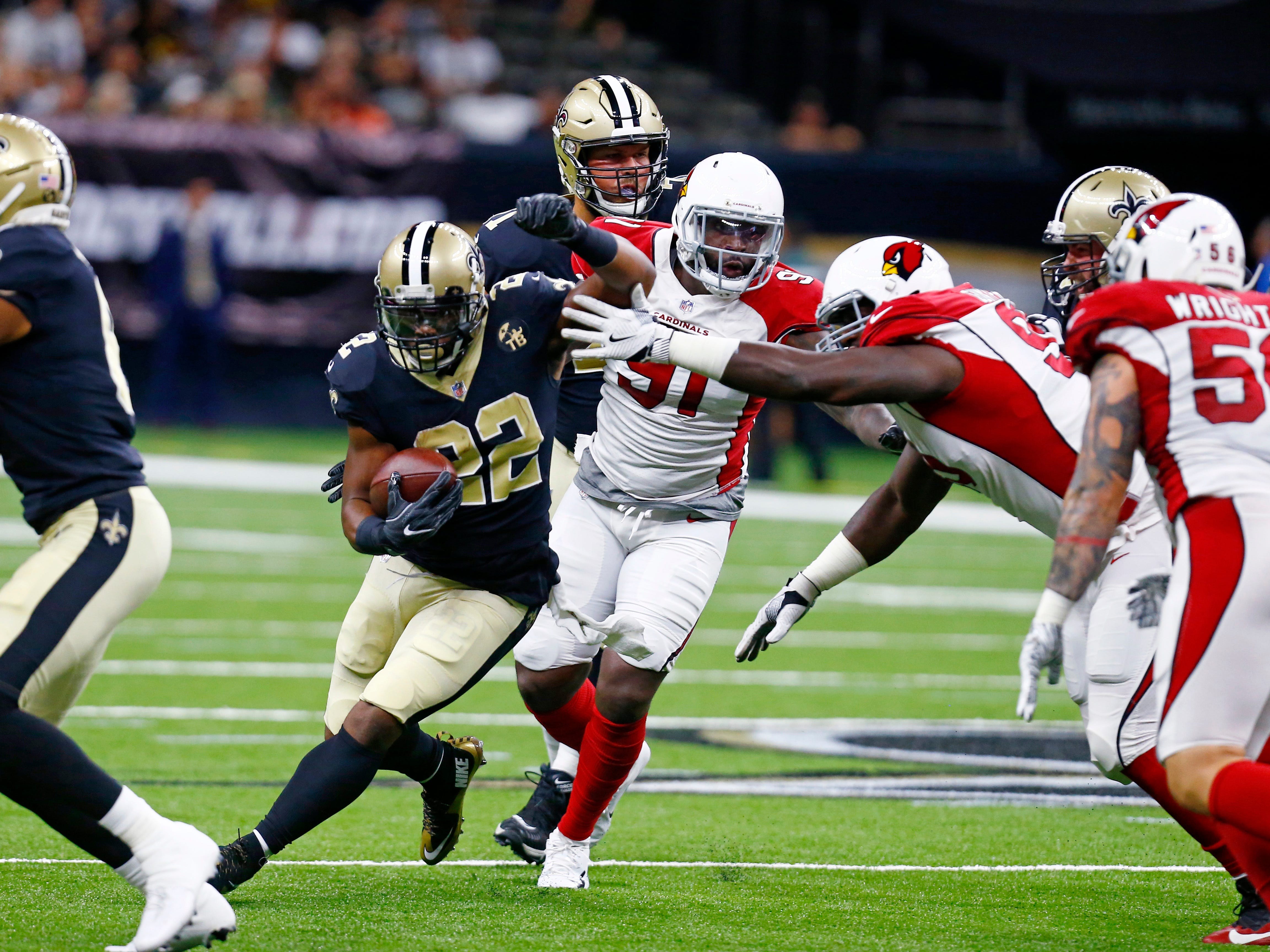 New Orleans Saints running back Mark Ingram (22) carries past Arizona Cardinals defensive end Benson Mayowa (91) in the first half of an NFL preseason football game in New Orleans, Friday, Aug. 17, 2018.