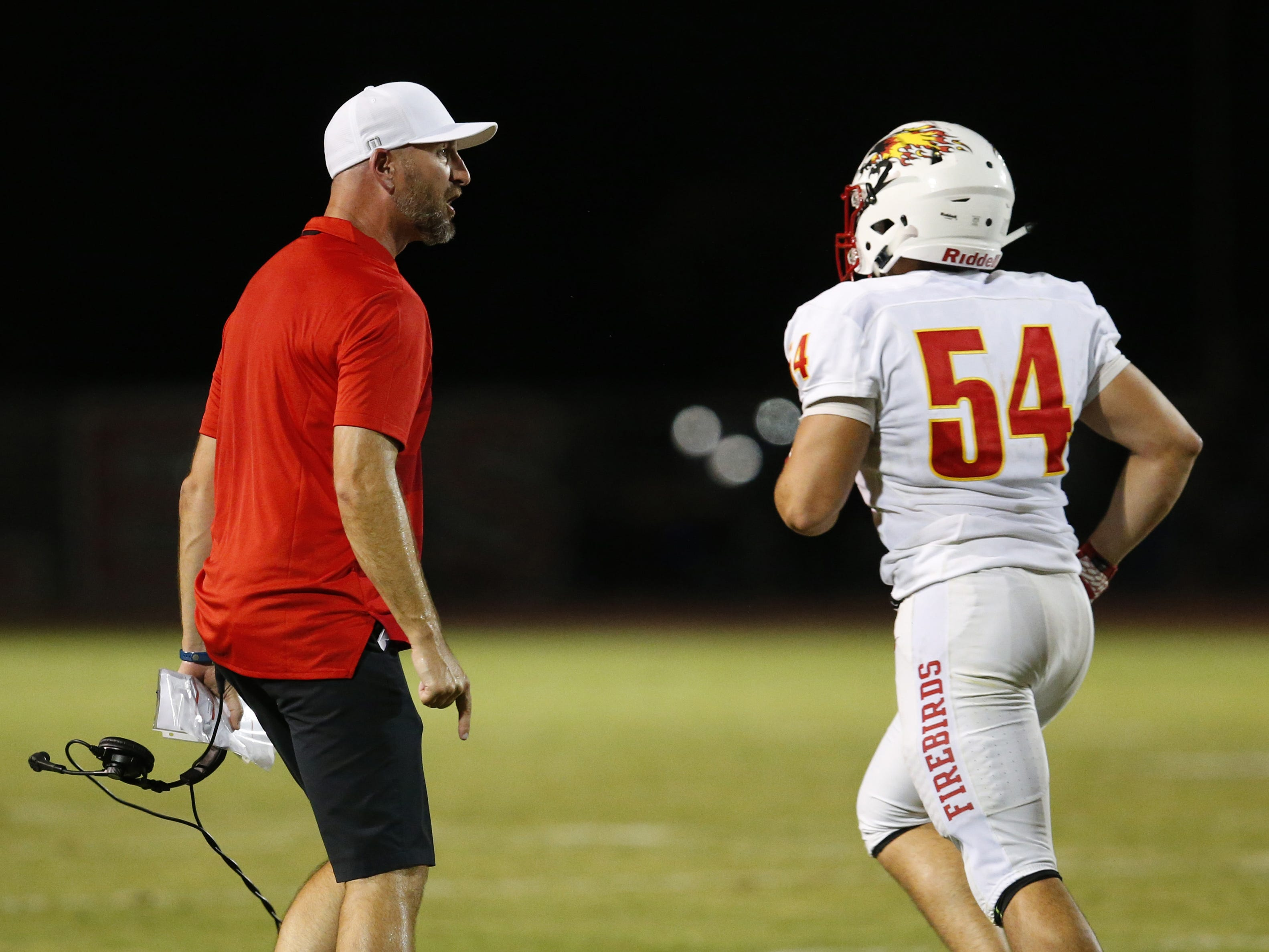 Chaparral head coach Brent Barnes talks to Chaparral Zien Tessler (54) during a high school football game against  Hamilton at Hamilton in Chandler on August 17, 2018. #hsfb