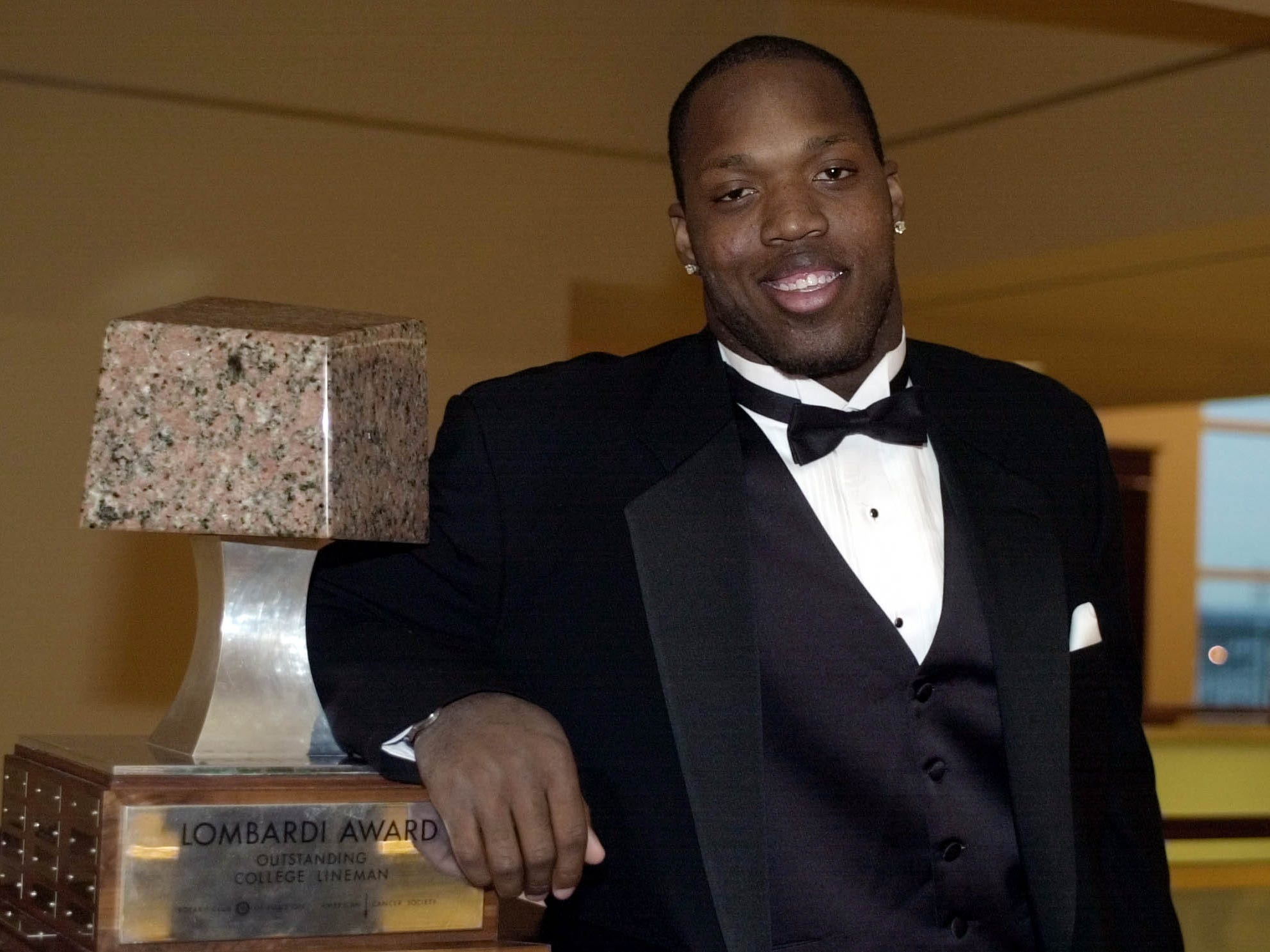 Arizona State defensive end Terrell Suggs poses with the Lombardi Award prior to the award presentation Wednesday, Dec. 11, 2002, in Houston. Suggs won the award, given to the nation's top collegiate lineman, Wednesday night.