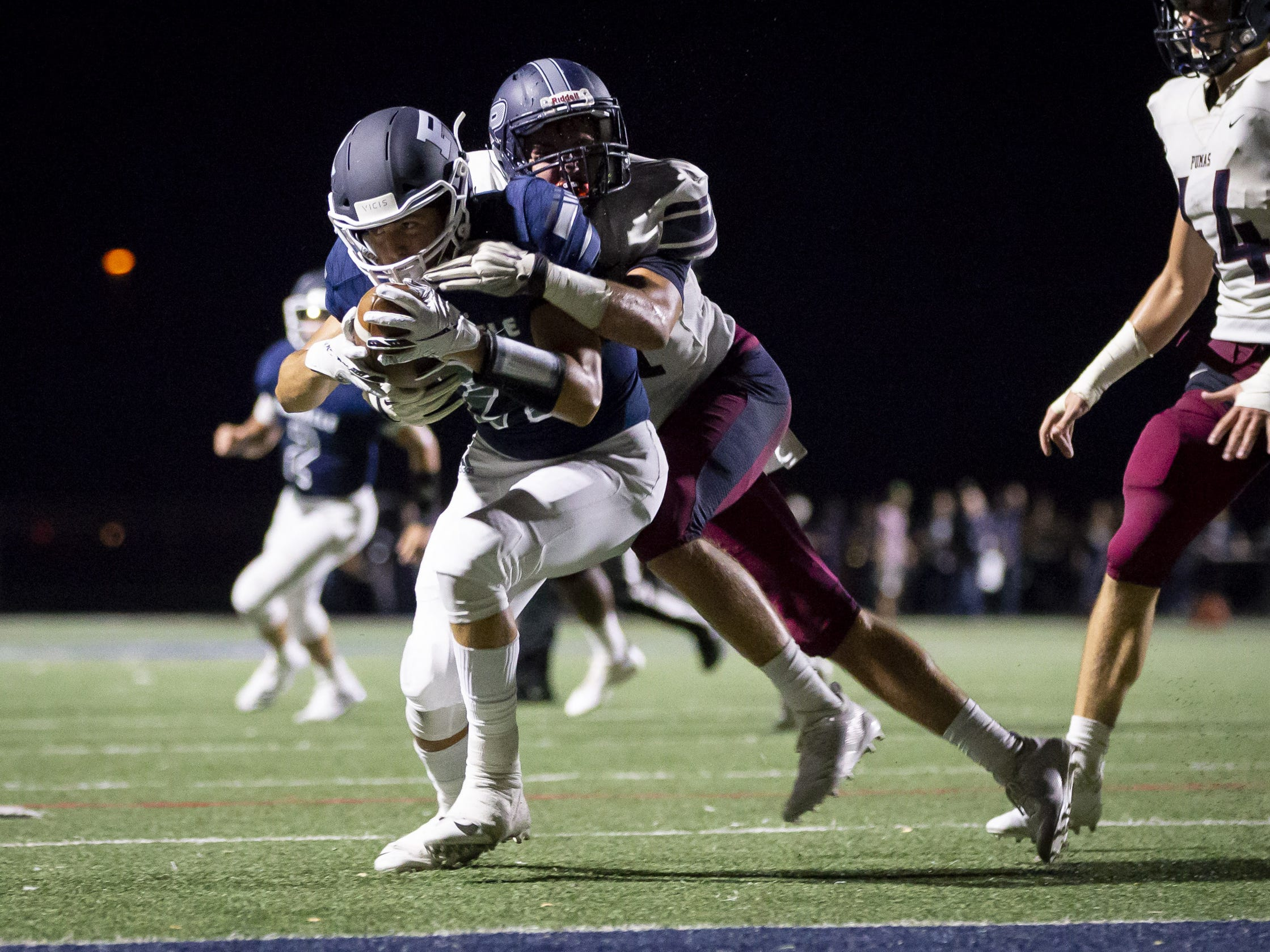 Wide receiver Jacob Brady (21) of the Pinnacle Pioneers is tackled by strong safety Kellen Simmons (31) of the Perry Pumas at Pinnacle High School on Friday, August 17, 2018 in Phoenix, Arizona.