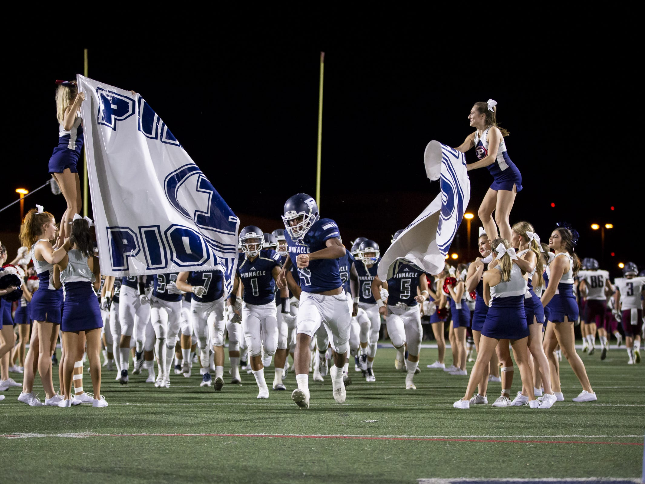 The Pinnacle Pioneers enter the field in the second half against the Perry Pumas at Pinnacle High School on Friday, August 17, 2018 in Phoenix, Arizona.